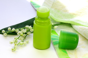 Lily of the valley, a towel and a green deodorant on the table