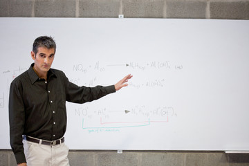 Professor standing at whiteboard with formula