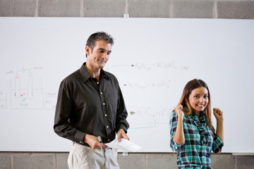 Professor giving student test at whiteboard