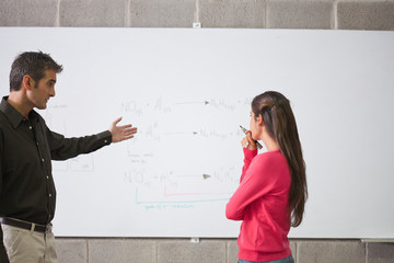 Professor standing with student at whiteboard