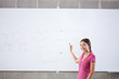 Smiling student standing at whiteboard with formula