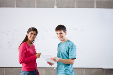 Two smiling students standing with test at whiteboard