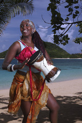 African musician plays the djembe rum at the beach