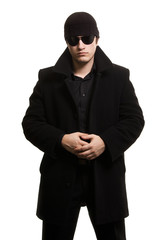 confidence man in black coat and sunglasses