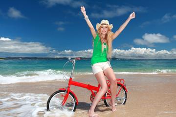 自転車に乗って両手を広げる笑顔の女性