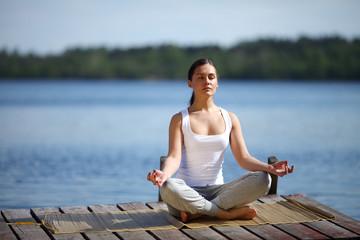 beautiful young girl training yoga near a lake