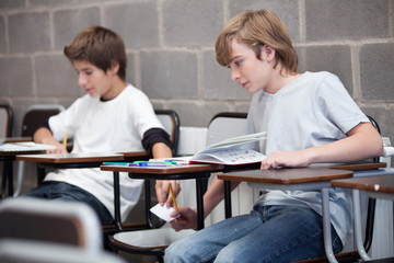 Two schoolboys cheating in classroom