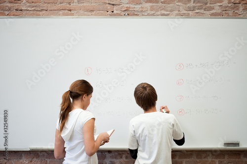 Boy and girl writing on whiteboard in classroom