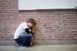 Depressed schoolboy crouching in classroom