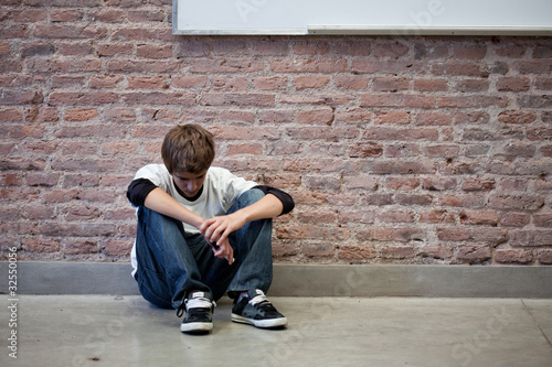 Depressed schoolboy sitting in classroom