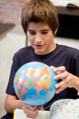 Schoolboy looking at globe in classroom