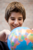 Smiling schoolboy looking at globe