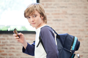Schoolboy with backpack using cell phone