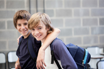 Two schoolboys standing arm in arm in classroom