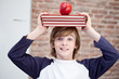 Schoolboy balancing books and apple on his head