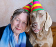 Portrait of a woman and dog with party hats