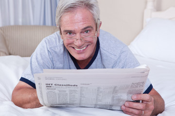 Smiling senior man reading newspaper in bed