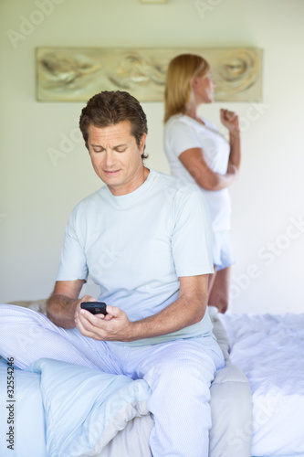 Man in bedroom holding cell phone with woman in background