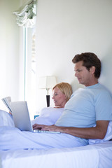 Mature couple with laptop and newspaper in bed