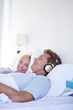 Woman looking at husband with headphones in bed