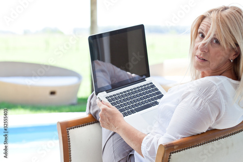 Mature woman using laptop outdoors