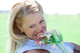 Mature woman smelling at flowers outdoors
