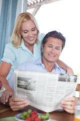 Mature couple reading newspaper at table