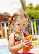 Child girl in glasses and red bikini drink juice.