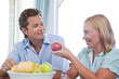 Mature couple eating fruit at home