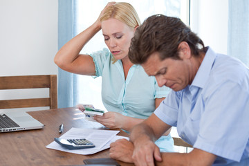 Despaired mature couple at home paying bills