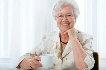 Beautiful senior woman enjoying a cup of tea or coffee