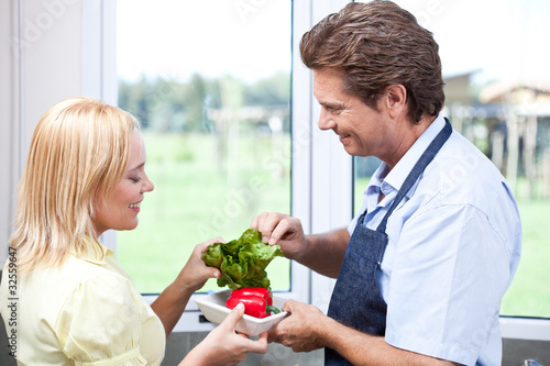 Mature couple in kitchen preparing healthy food