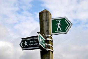 3 green footpath signs pointing in different directions