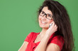 Portrait of young smiley female in eye-glasses talking on phone