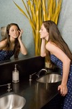 A Young Woman Looking At Herself In A Bathroom Mirror