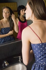 Two Young Women Looking At Themselves In A Bathroom Mirror