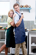 Mature couple wearing aprons in kitchen