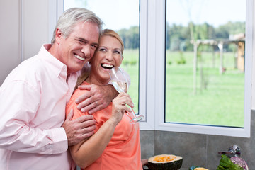 Laughing mature couple drinking champagne in kitchen
