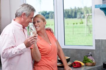 Happy mature couple drinking champagne in kitchen