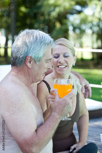 Mature couple in swimwear embracing with drinks