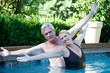 Mature couple with outstretched arms in swimming pool