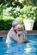 Happy mature couple hugging in swimming pool