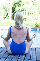 Woman practicing yoga by the poolside