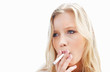 Young female smoking a cigarette against white background