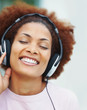 Closeup of a happy young girl enjoying music over headphones