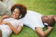 Happy young couple listening to romantic music on grass