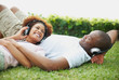 Happy couple listening to music together on the grass outdoors