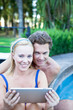 Mature couple with tablet computer by the poolside