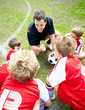 Football coach motivating little players before a match on field