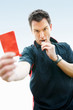 Football referee showing you the red card against sky